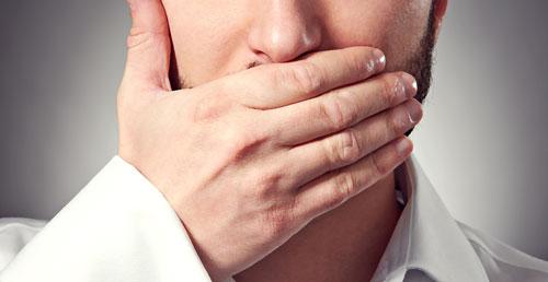 رجل يغلق فمه بيده لكي لا يتكلم