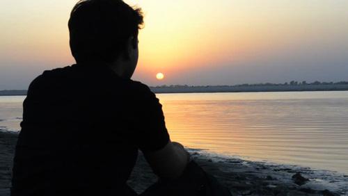 شاب يفكر وينظر الى النهر
