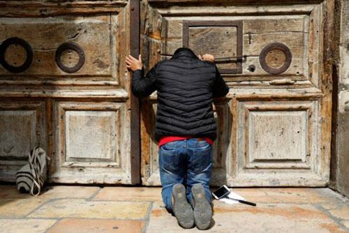 رجل يصلي امام باب كنيسة القيامة المغلق